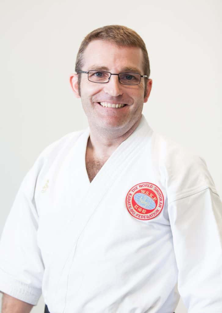 head and shoulder shot of man in glasses in karate uniform smiling at the camera