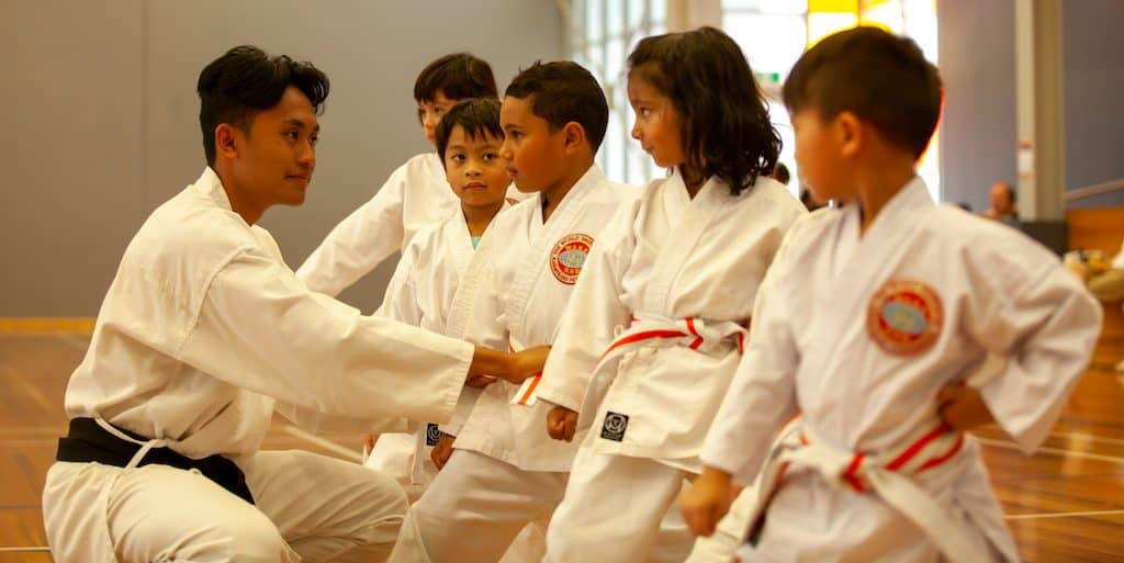black belt intructor showing a group of little tiger students how to stand correctly