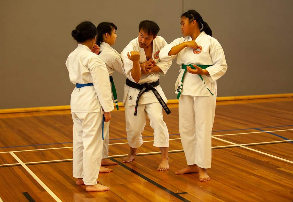 A picture of Eric teaching 3 students, two green belts and one blue belt
