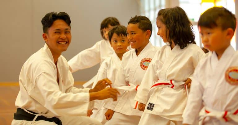 black belt intructor laughing with a group of little tiger students