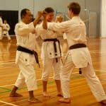 black belt intructor showing two brown belts how to perform and get out of a strangle hold