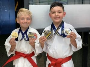 smiling young boys both showing their silver and gold medals