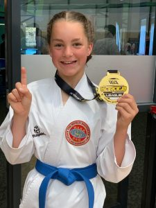 smiling young girl showing her first place competition medal