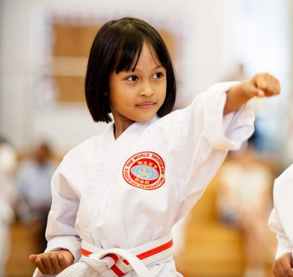 5 year old girl in a white karate uniform punching with left fist to the top right of the picture looking focused.