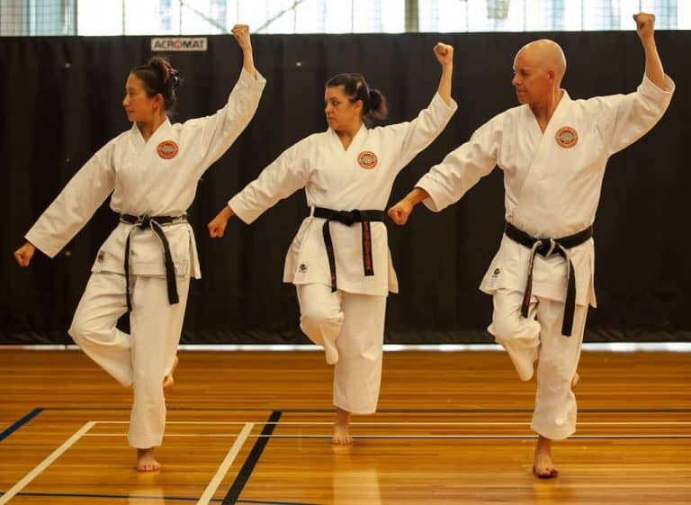 group of blackbelts doing manj-uke on one leg during kata