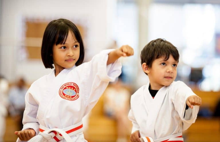 young boy and girl in a white karate uniform punching with left fist to the top right of the picture looking focused.