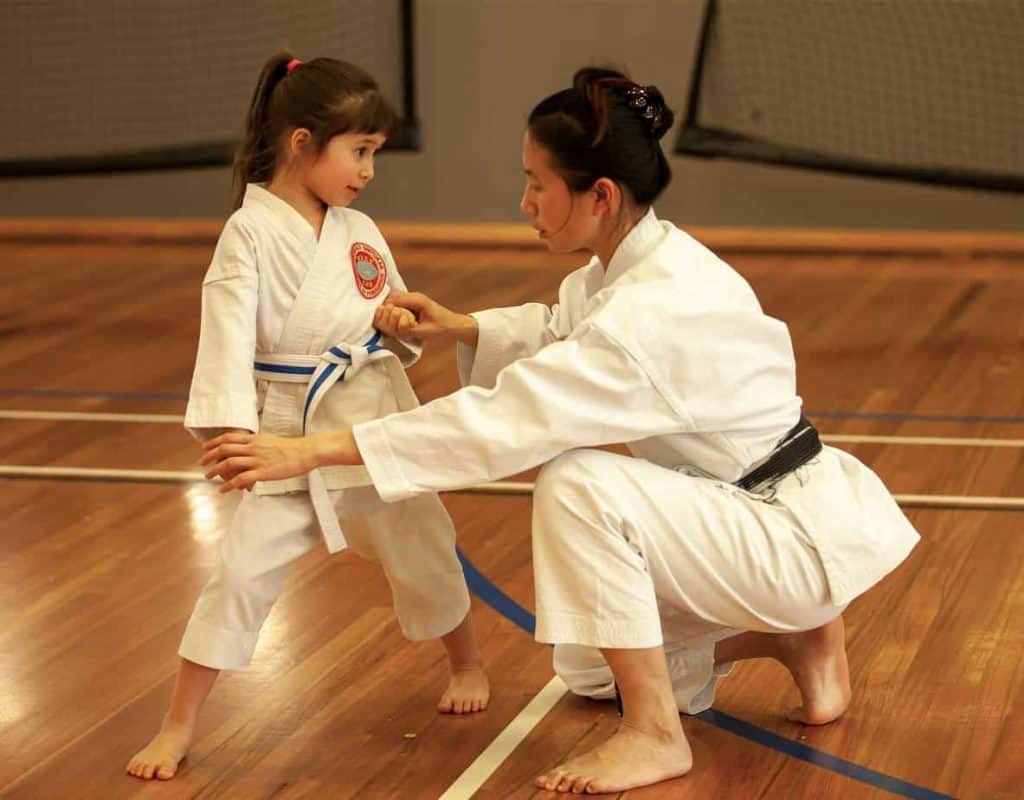 black belt karate mother showing daughter how to block strongly