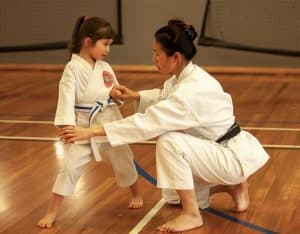 family training together black belt karate mother showing daughter how to block strongly