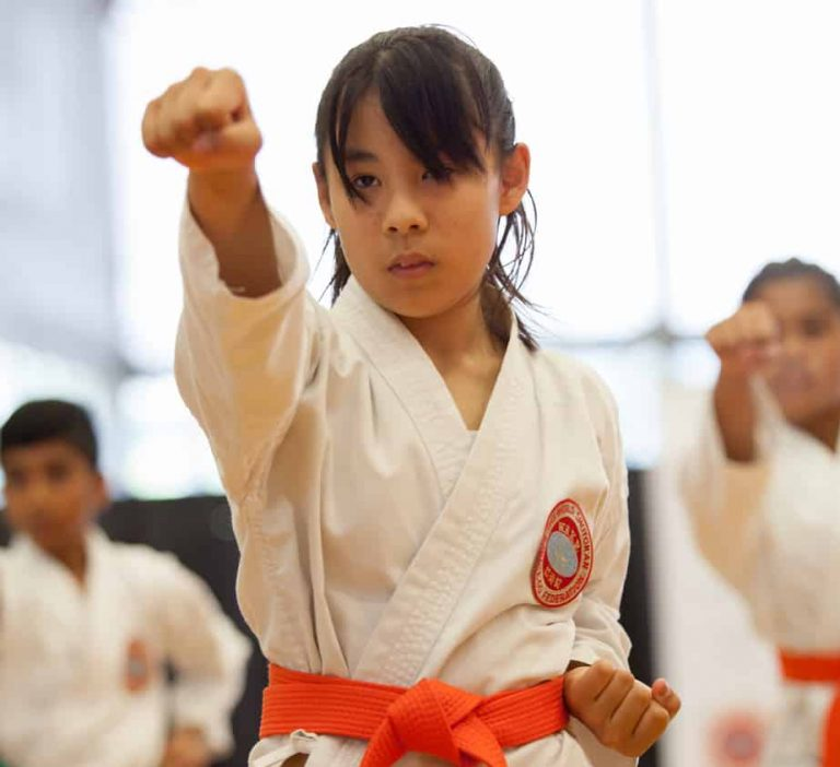 junior girl showing a focused head punch