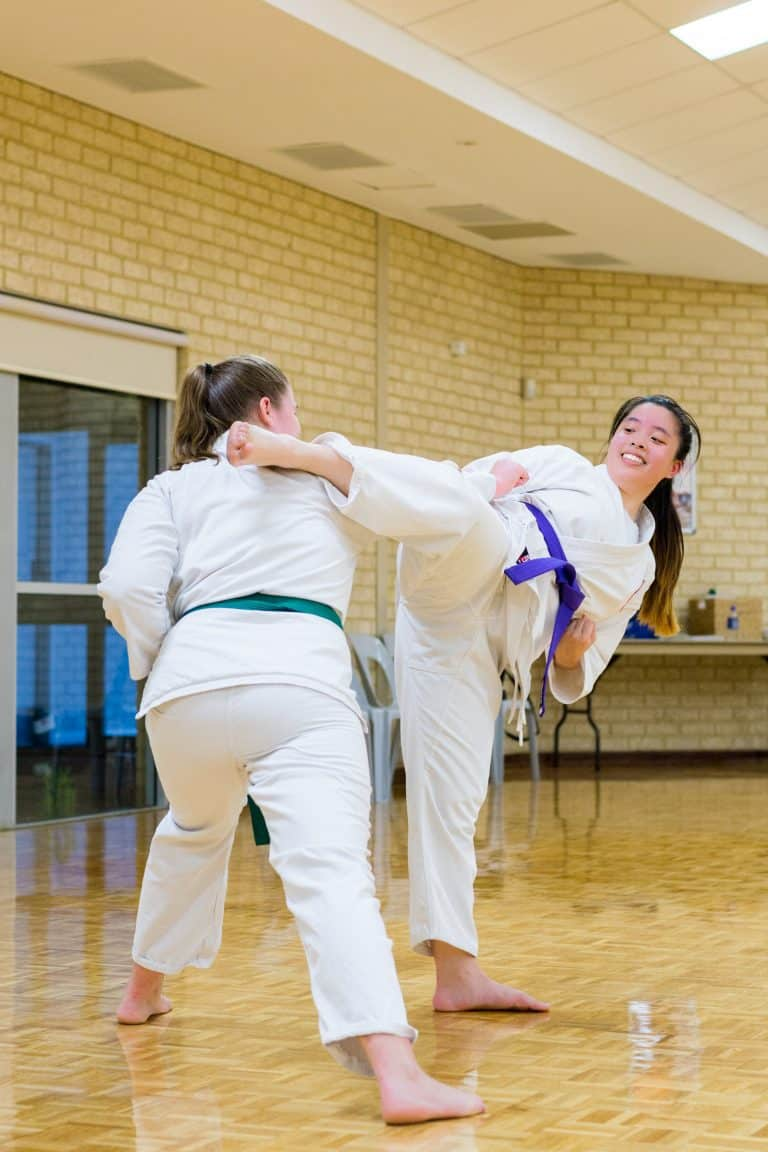 young girls practicing timing with a hook kick