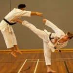 teenage brown belt side kicking black belt