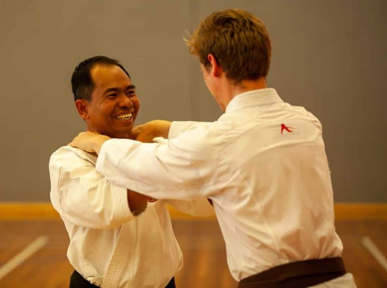 black belt demonstrating how to get out of a strangle hold