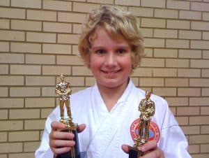 smiling young boy holding two first place competition trophies