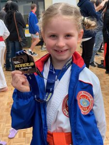 smiling young girl holding third place medal