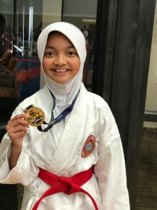 smiling girl holding gold competition medal