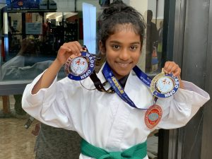 smiling young girl holding a first and third place completion medal
